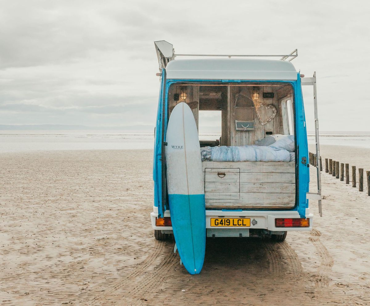 A blue and white camper has its rear doors open. A bed sits on a storage platform, a surf board rests next to the bed, and the camper sits on a sandy, bright beach.