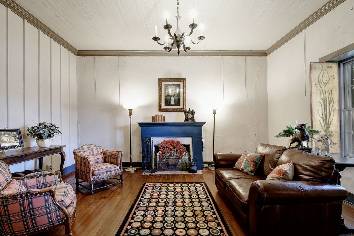 A living room with leather couch, two plaid chairs, and a blue fireplace.