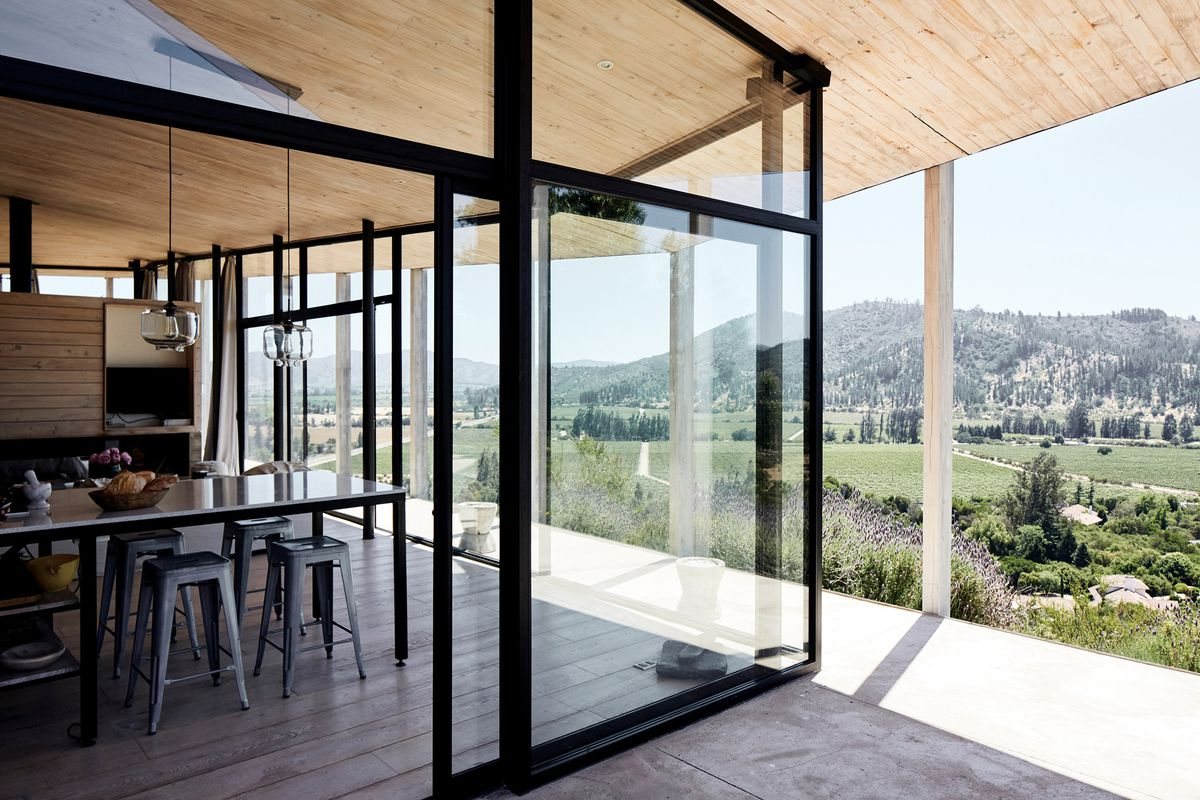 A dining area surrounded by glass walls, which open out onto a terrace and wine country views.