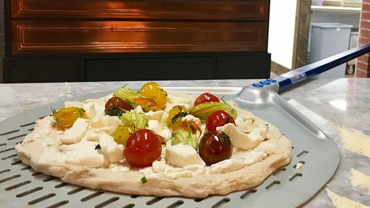 A Keste pizza dough with tomatoes on it, in front of an oven.