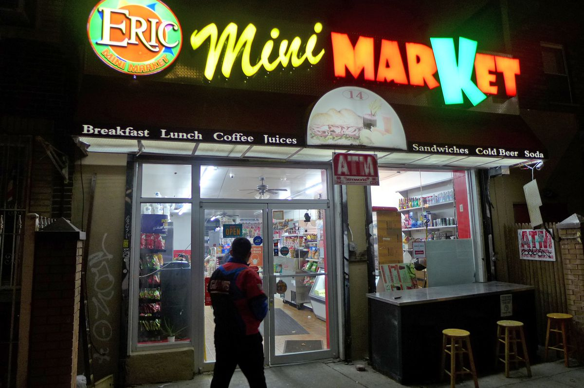 The dark outside of a bodega with bright signage in several jumbled fonts.