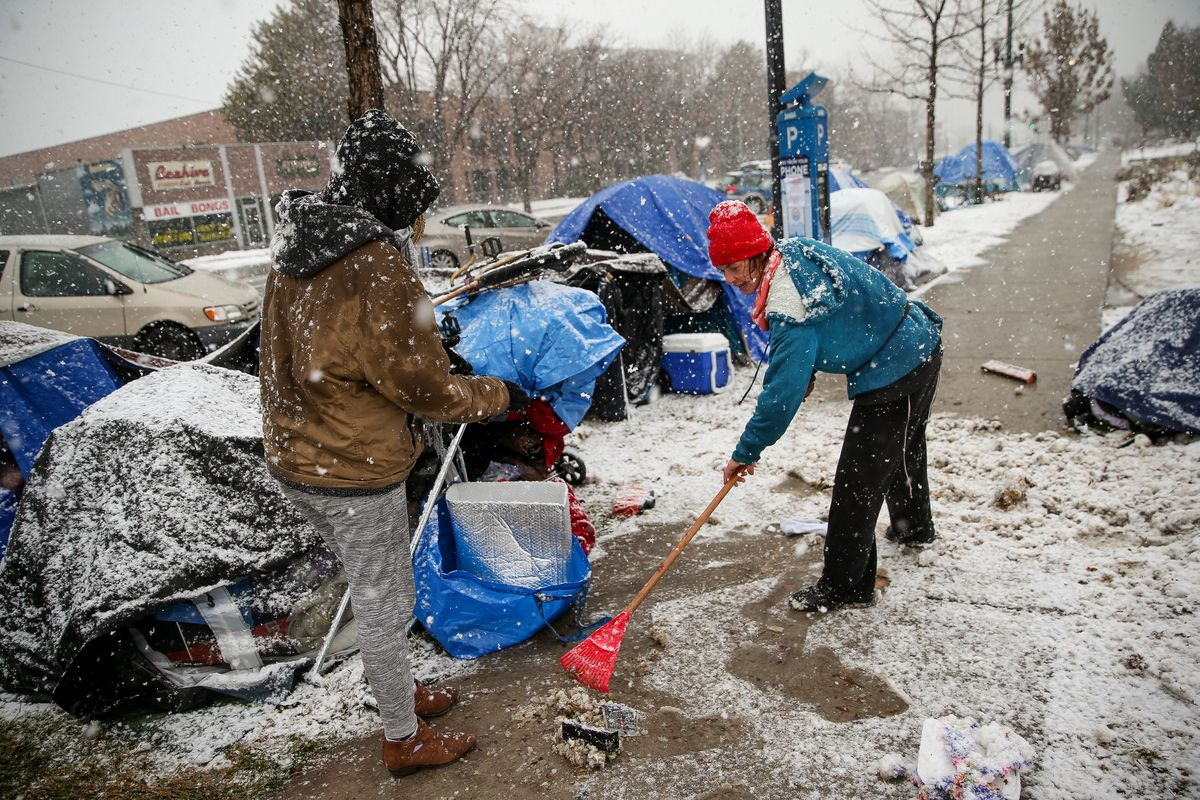 Awate Oliver, 19, left, and Sara Entwhistle, 30, who are homeless, talk as Entwhistle clears snow from the sidewalk where many people who are homeless are camping along 500 South at Library Square in Salt Lake City on Friday, Nov. 29, 2019. Entwhistle said she wants to keep the sidewalk clear of snow to be a good steward of the area they are occupying.