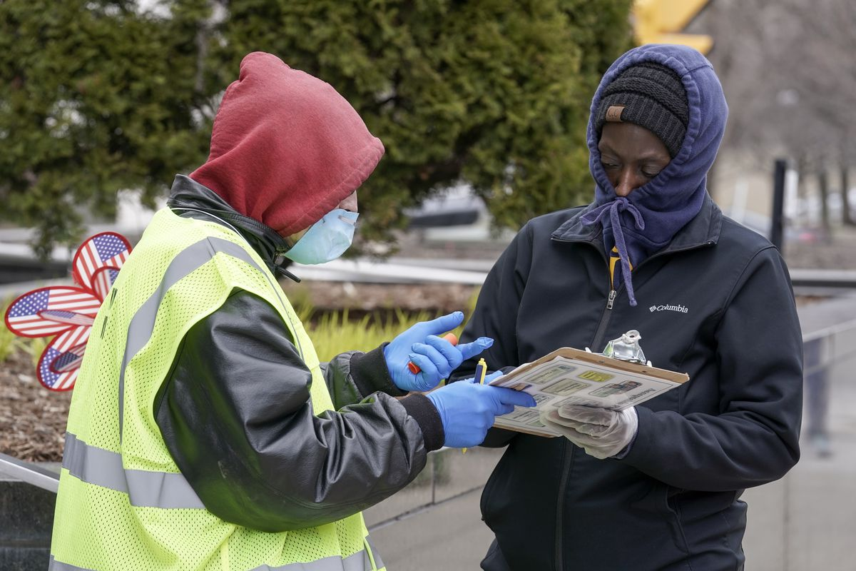 A poll worker in gloves and a mask points as a clipboard; a voter in gloves with his hoodie tied over his nose and mouth listens.