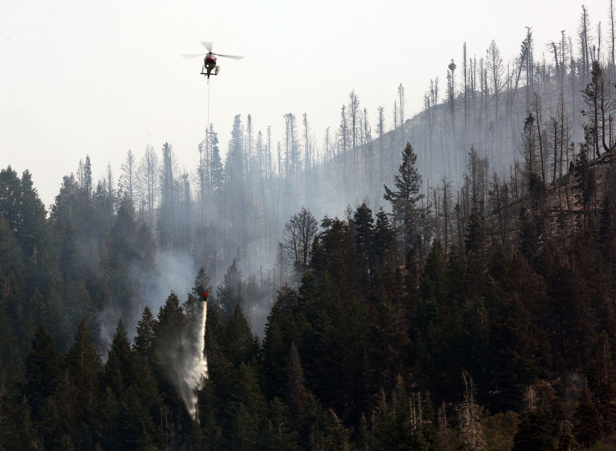 A helicopter drops water as crews continue fighting the Parley's Canyon Fire near Park City on Sunday, Aug. 15, 2021.