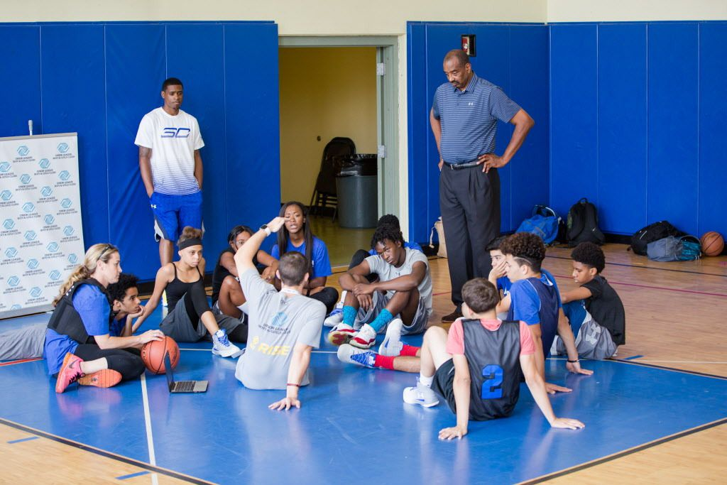 """Former NBA player Wallace """"Mickey"""" Johnson (standing at right) talks to kids in the """"Building Bridges Through Basketball"""" program. He talked about growing up in North Lawndale, and about how an officer in his community helped him stay on the straight and"""
