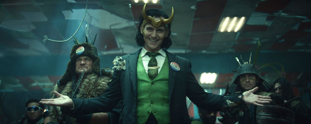 """Loki (TomHiddleston) in Marvel Studios' Loki, dressed in a tattered suit, a horned helmet, and a button that says """"VOTE LOKI."""""""