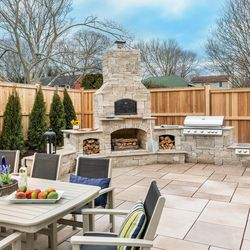 Protected by a tall privacy fence and by arborvitae shrubs that will grow in to create a hedge, the hearth provides a visual focal point for the outdoor kitchen and dining area. An eight-person dining table leaves plenty of patio space for family and guests to mingle. <em>Masonry contractor: </em><a class=