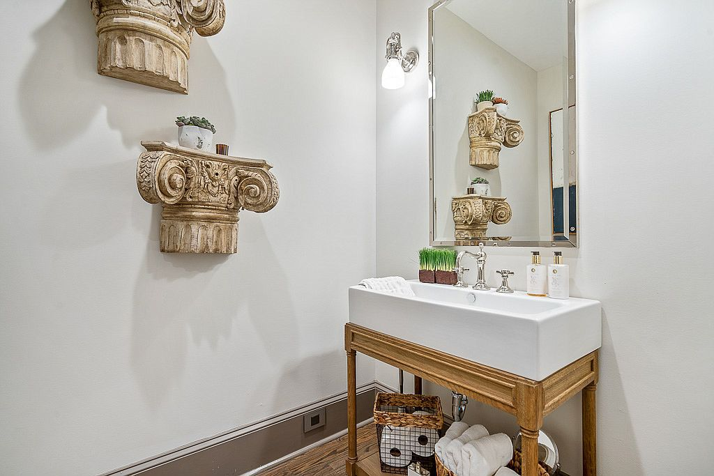 A small white bathroom with the tops of columns on the wall.