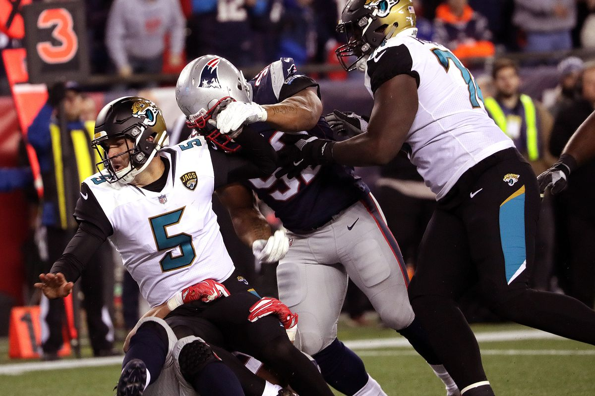 Jacksonville Jaguars quarterback No. 5 Blake Bortles is sacked by a New England Patriots defensive lineman.