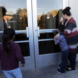 Monica Vakaafi and her son, Matai, look in a door as they wait to pick up a student at Mountain View High School in Orem on Tuesday, Nov. 15, 2016, after five students were stabbed in an apparent attack by a 16-year-old boy.