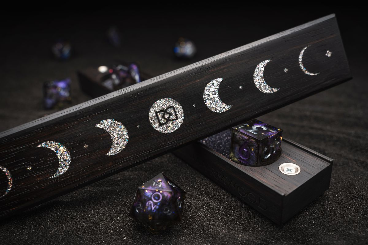 A phases of the moon motife, rendered in opalescent flake, supported by purple and black transparent dice.