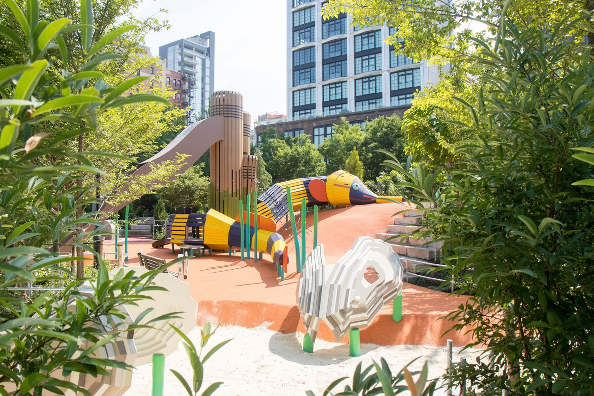 A play area with water toys. There are trees in the foreground and city buildings in the distance.
