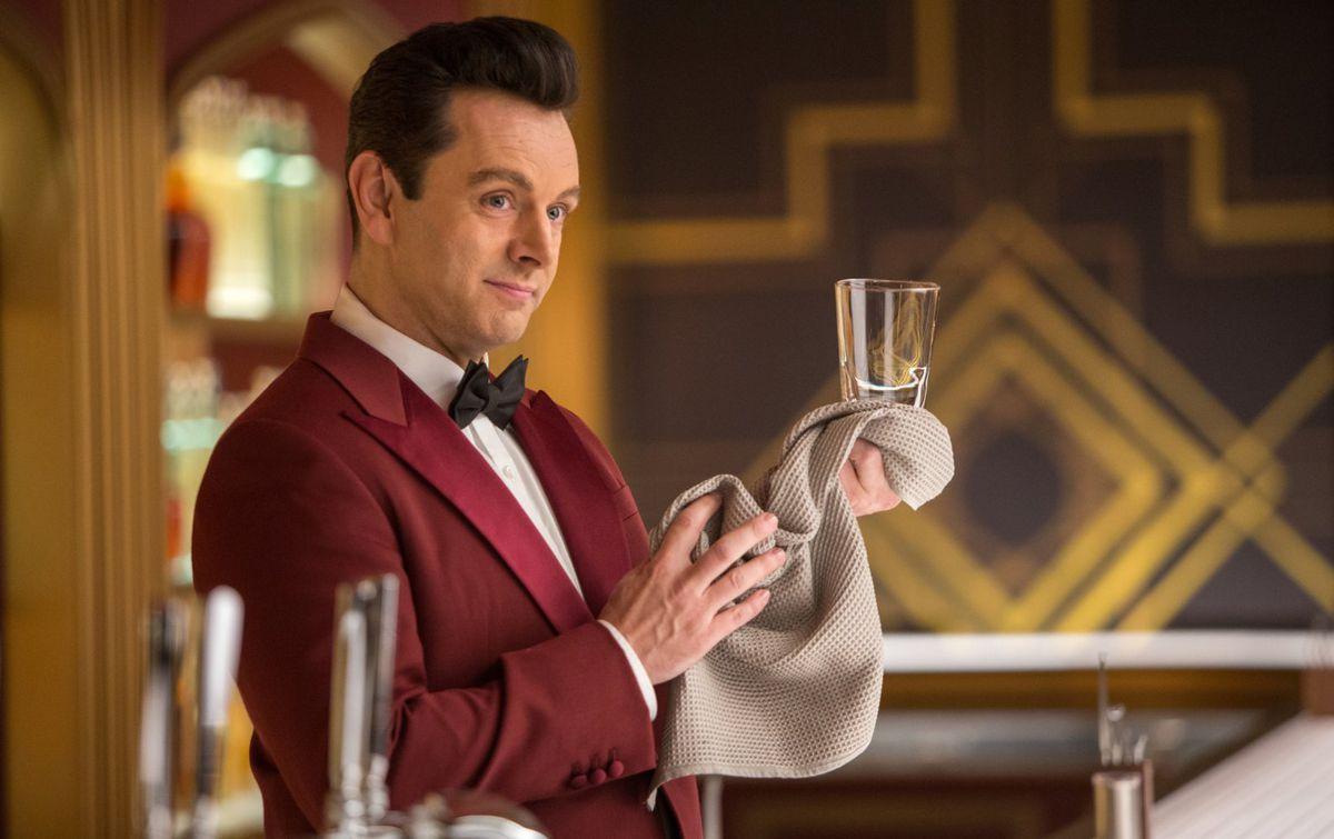 Michael Sheen polishes a glass as a robot bartender in Passengers