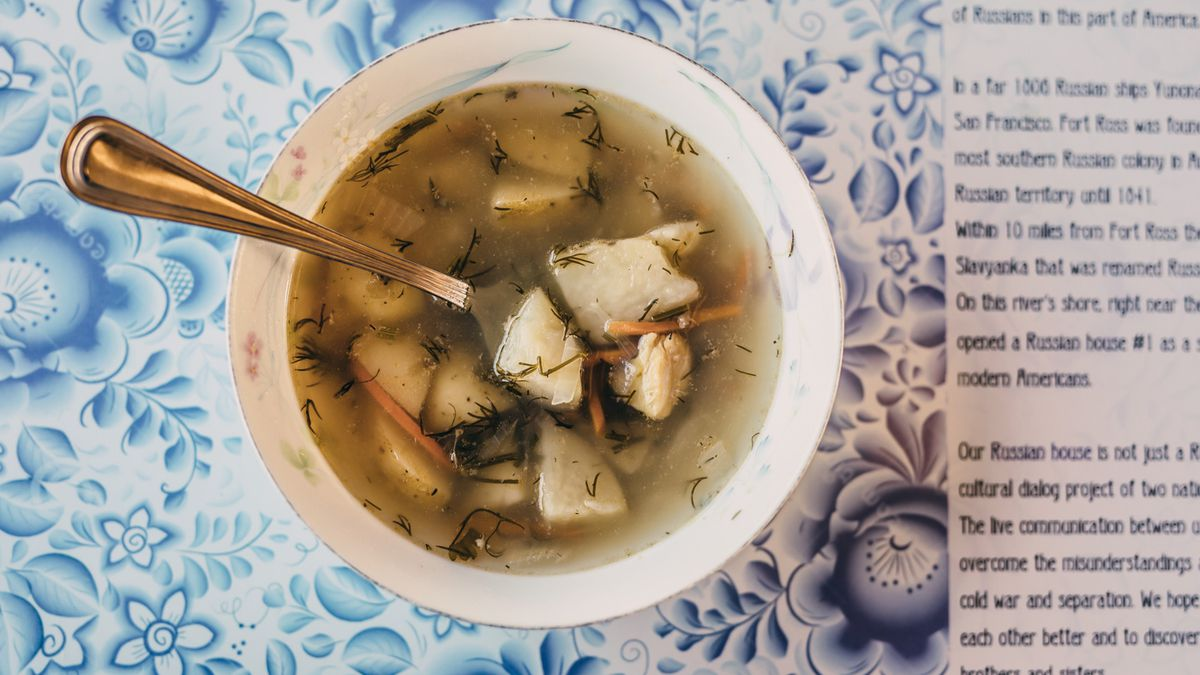 A clear fish soup with chunks of potatoes