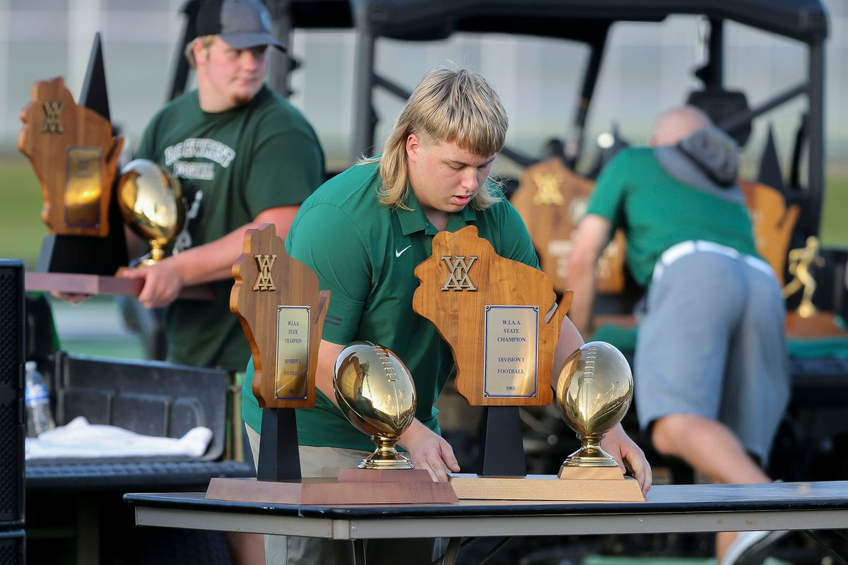 Jack Johnson places a state championship trophy on display before a celebration ceremony for the late Wayne Steffenhagen