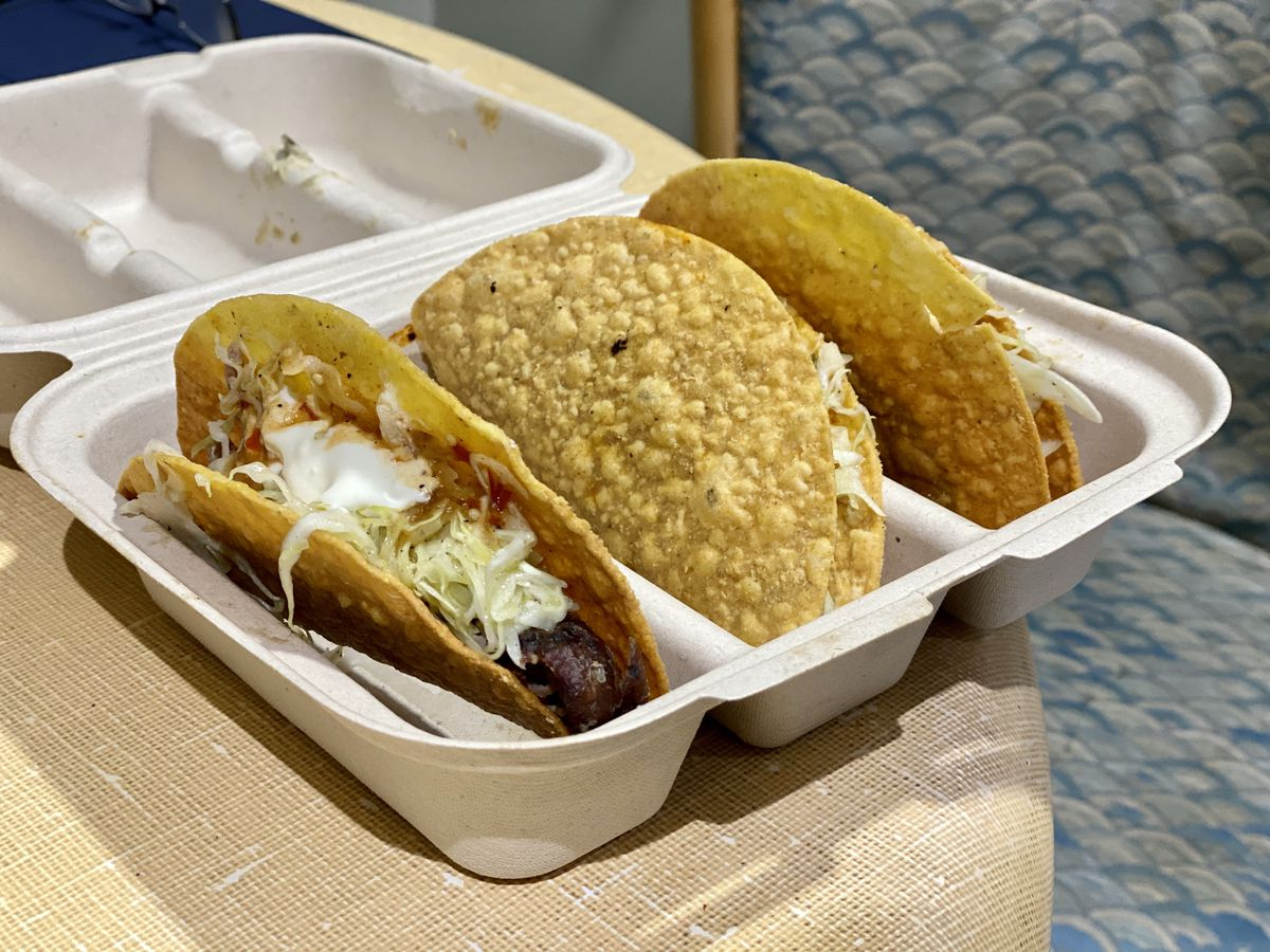 Three hard shell corn tacos from Taco Bay sit in a white takeout container