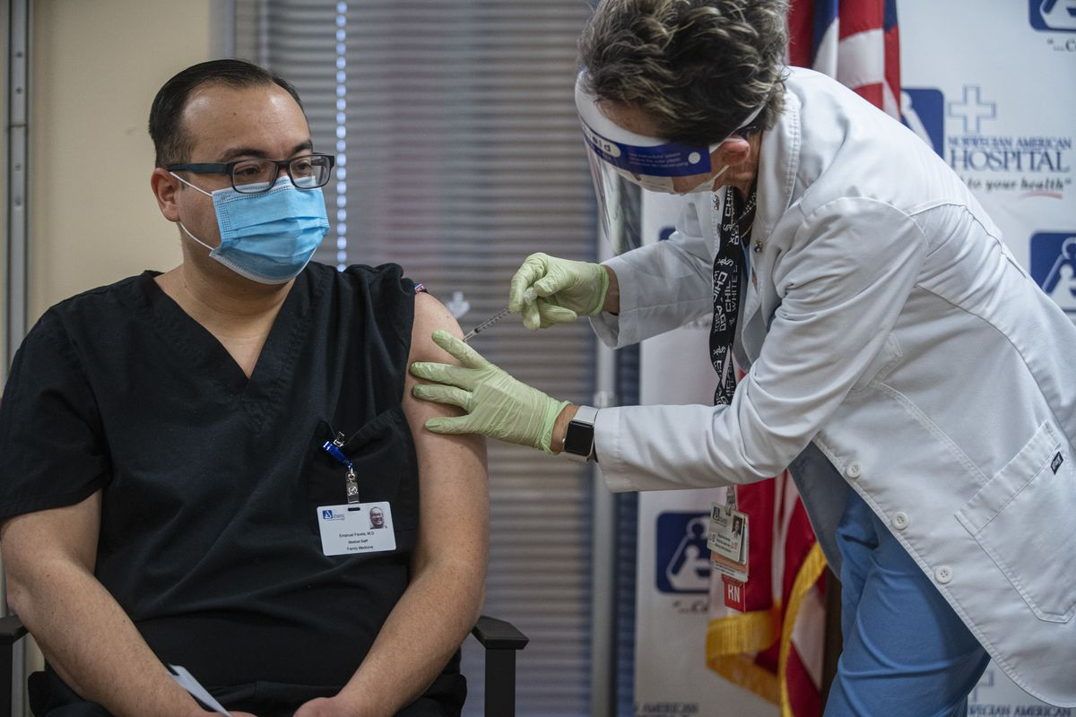 Dr. Emanuel Favela is vaccinated at a press conference to administer the first COVID-19 vaccinations to Latino healthcare workers at the Norwegian American Hospital in Humboldt Park.