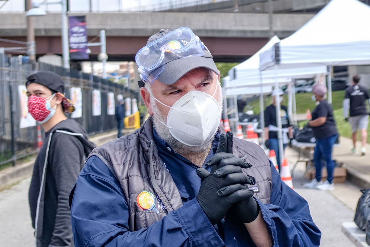 A Masked chef Jose Andres stands with his hands clasped