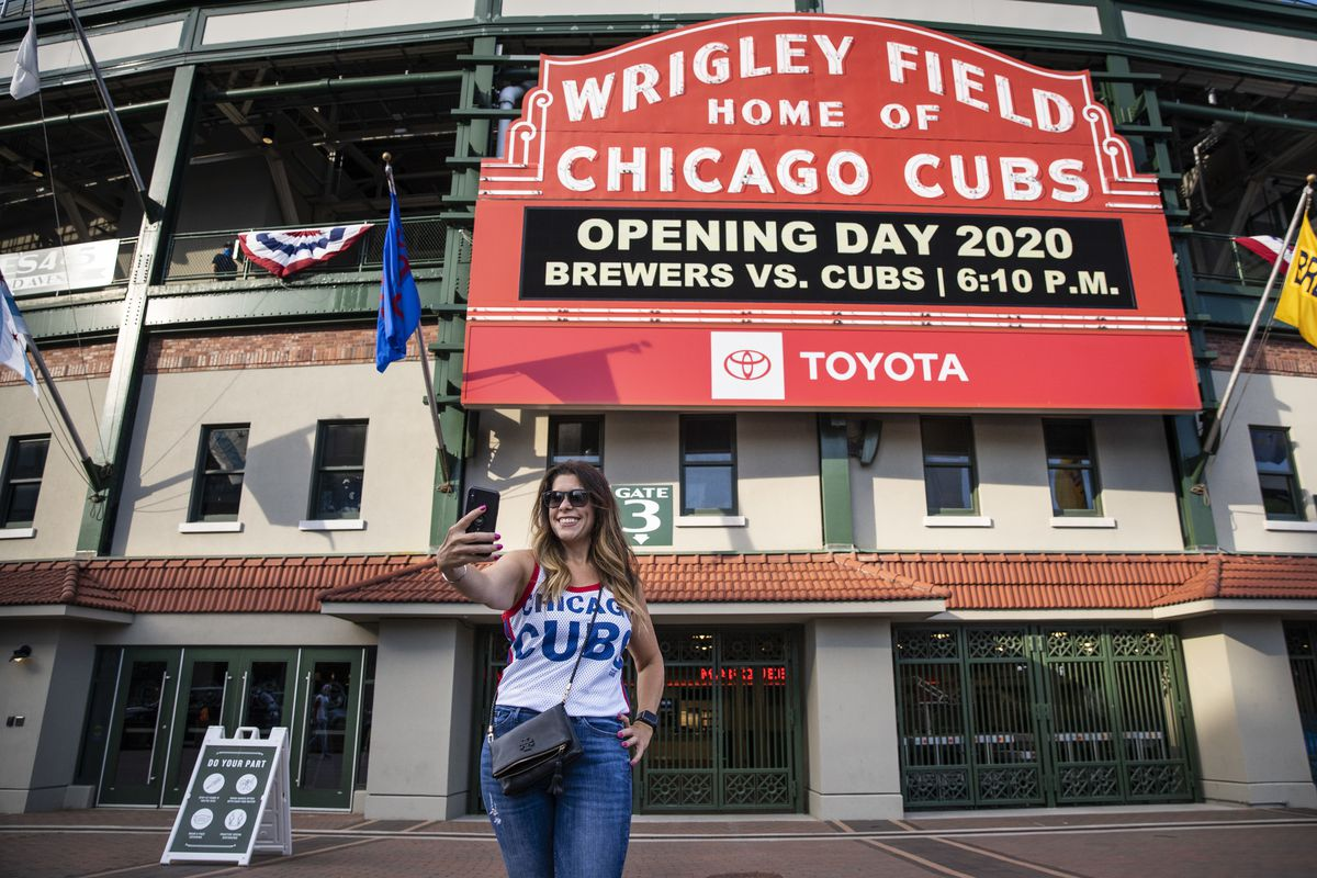 Fans take selfies outside Wrigley Field shortly before the start of the opening day game between the Chicago Cubs and the Milwaukee Brewers, Friday evening, July 24, 2020.