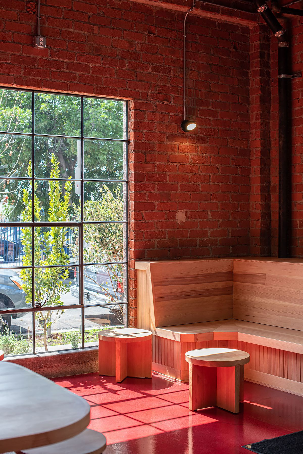 A big window and wooden tables inside of a new cafe.