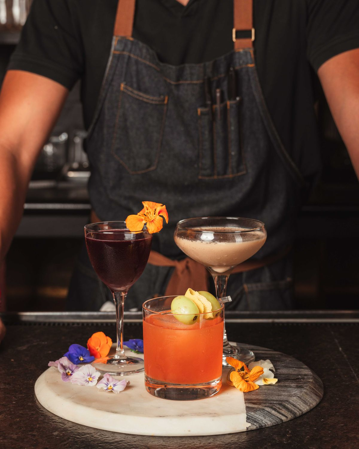 A bartender in a black t-shirt and denim apron is visible from the neck down, standing behind a bar on which there are three fancy cocktails displayed on a white and marble tray. Edible florals garnish the drinks and the tray.