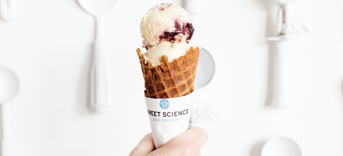 A hand holds a cone in front of a white wall covered with white ice cream scoops