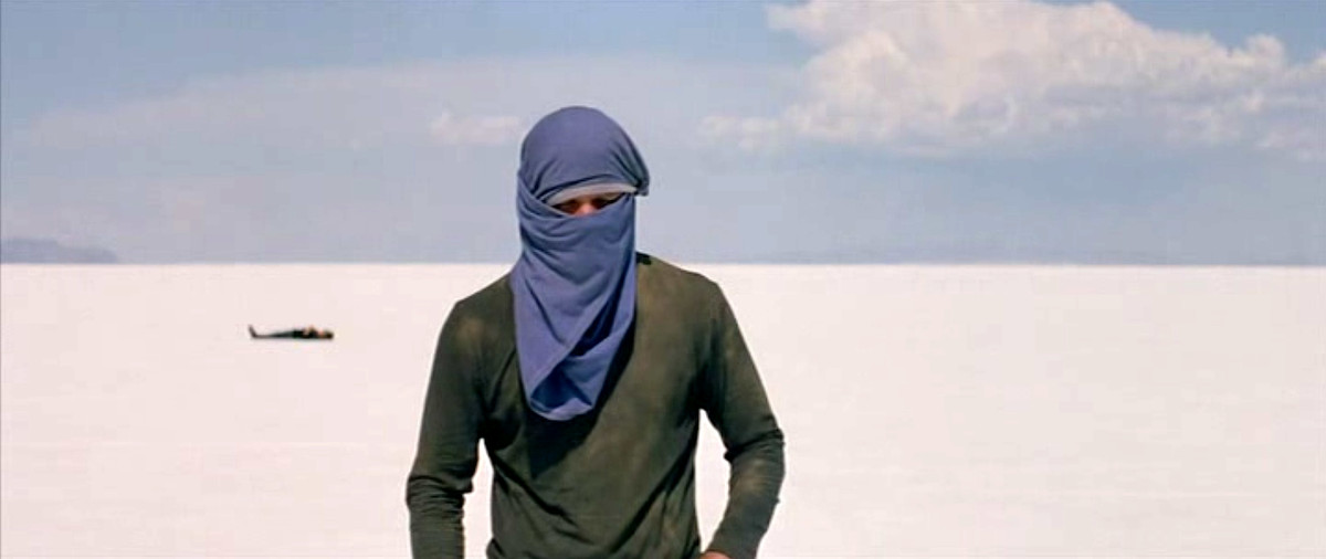 One of two friends toils through the desert in Gerry with a shirt over his head, as his friend lies out of focus in the sand behind him.