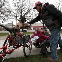 Fred Rivers pushes his dog Diamond down as he, Lakota Beal and Todd Jr. Dickerman get ready to leave the 10th annual Community Coat Exchange at Pioneer Park in Salt Lake City on Friday, Nov. 28, 2014. They all found coats.