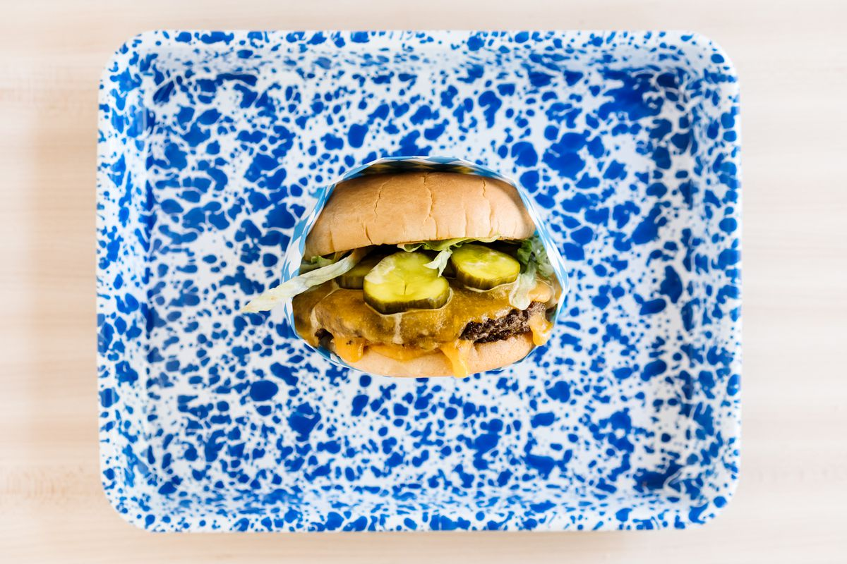 A cheeseburger with pickles sits on a blue tray at Holler