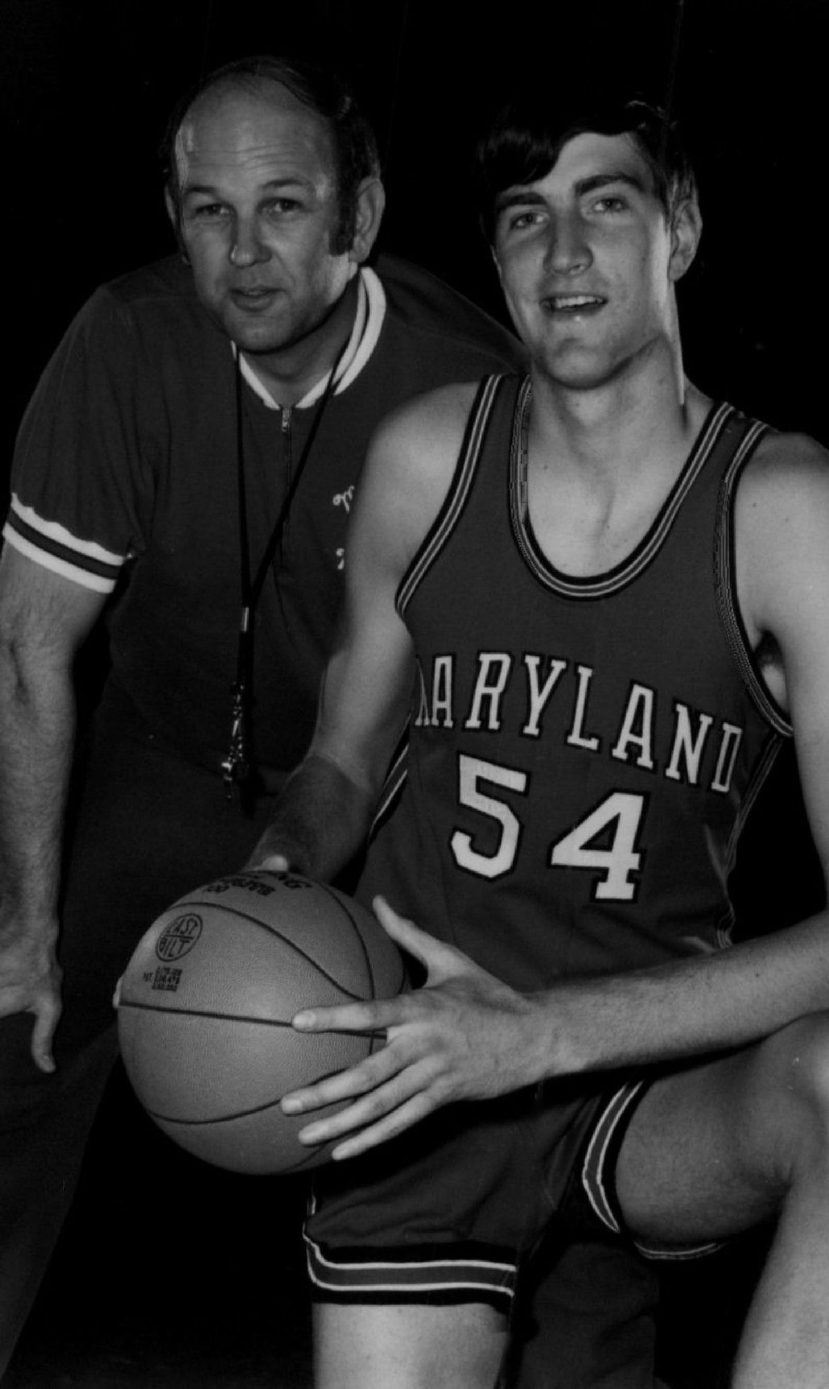 a black-and-white photograph of an older man wearing a coach's whistle and a younger man, holding a basketball, in a basketball uniform.