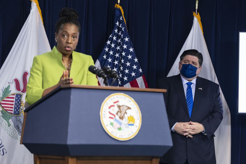 Gov. J.B. Pritzker listens as state Public Health Director Dr. Ngozi Ezike briefs the media on Thursday.