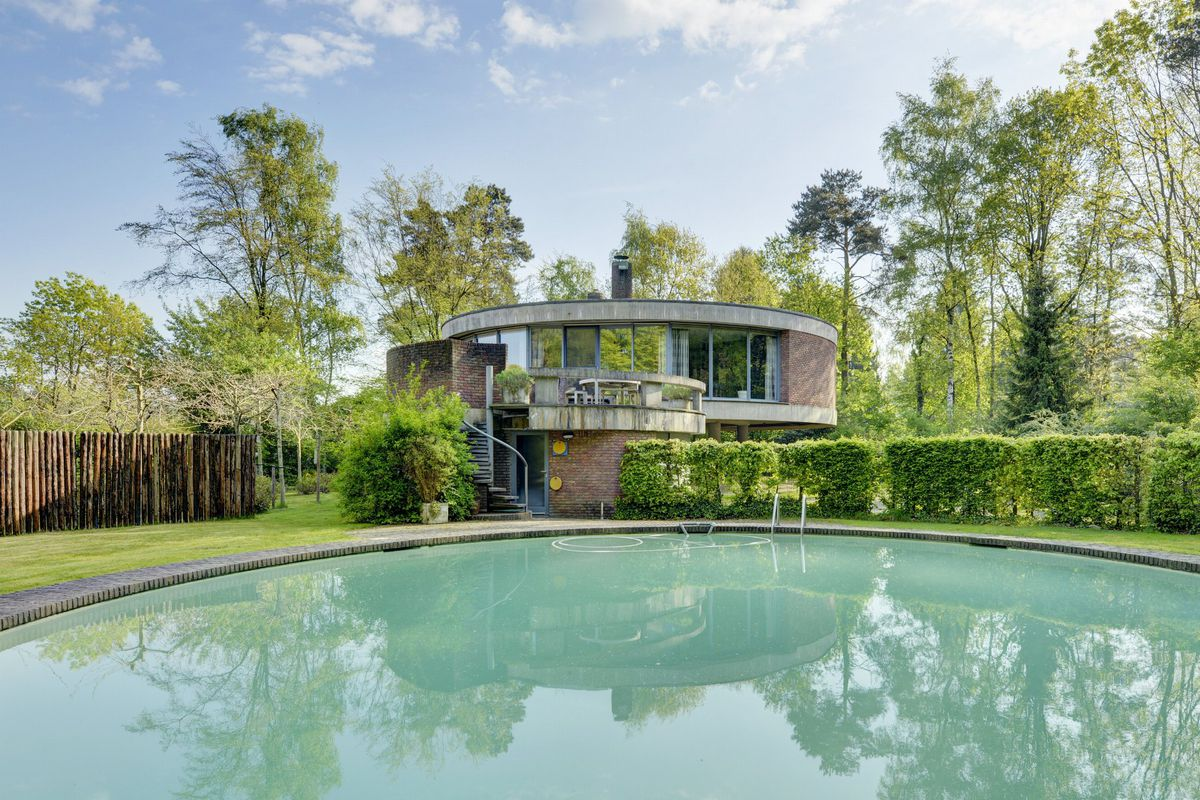Exterior shot of home with round pool in foreground and circular brick-and-concrete home in the background on green lot.