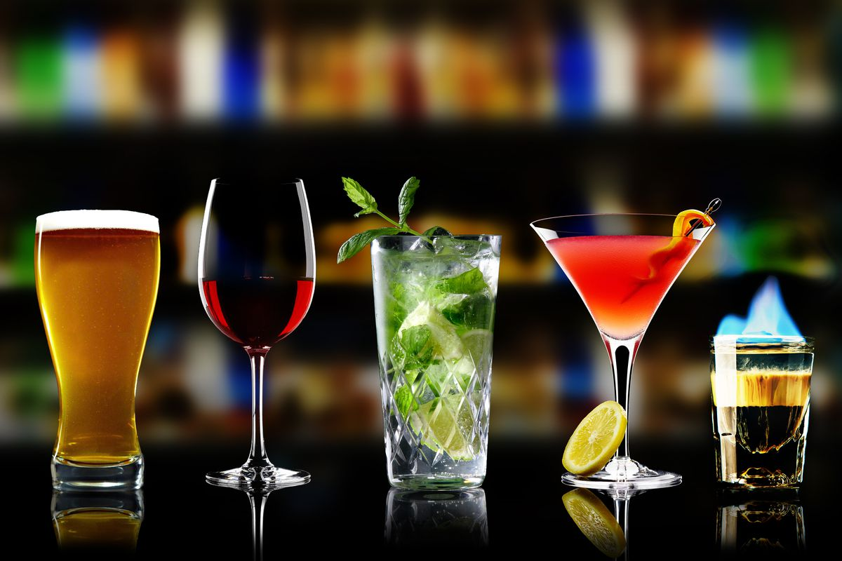 From left to right: a pint of beer, a glass of wine, a mojito, a Manhattan with an orange peel garnish, and a flaming shot of brown liquor are all lined up next to each other on a bar.