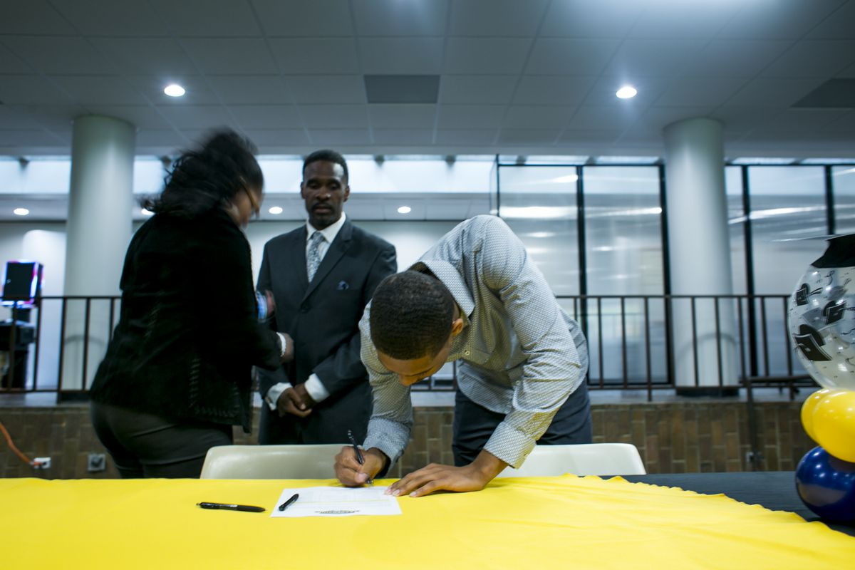 Demetrius Robinson signs a college pledge during a signing day ceremony for seniors at the Jalen Rose Leadership Academy, while his parents look on. Robinson is now a freshman at Central Michigan University.