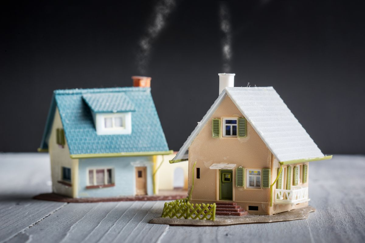 Two miniature houses against a black background.