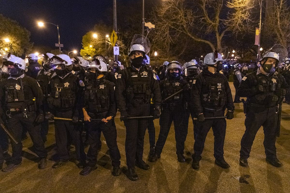Chicago police form a line with batons out after an earlier clash with protesters near Logan Square Park in Chicago Friday, April 16, 2021, a day after the release of video that shows a Chicago police officer fatally shoot a 13-year-old last month.