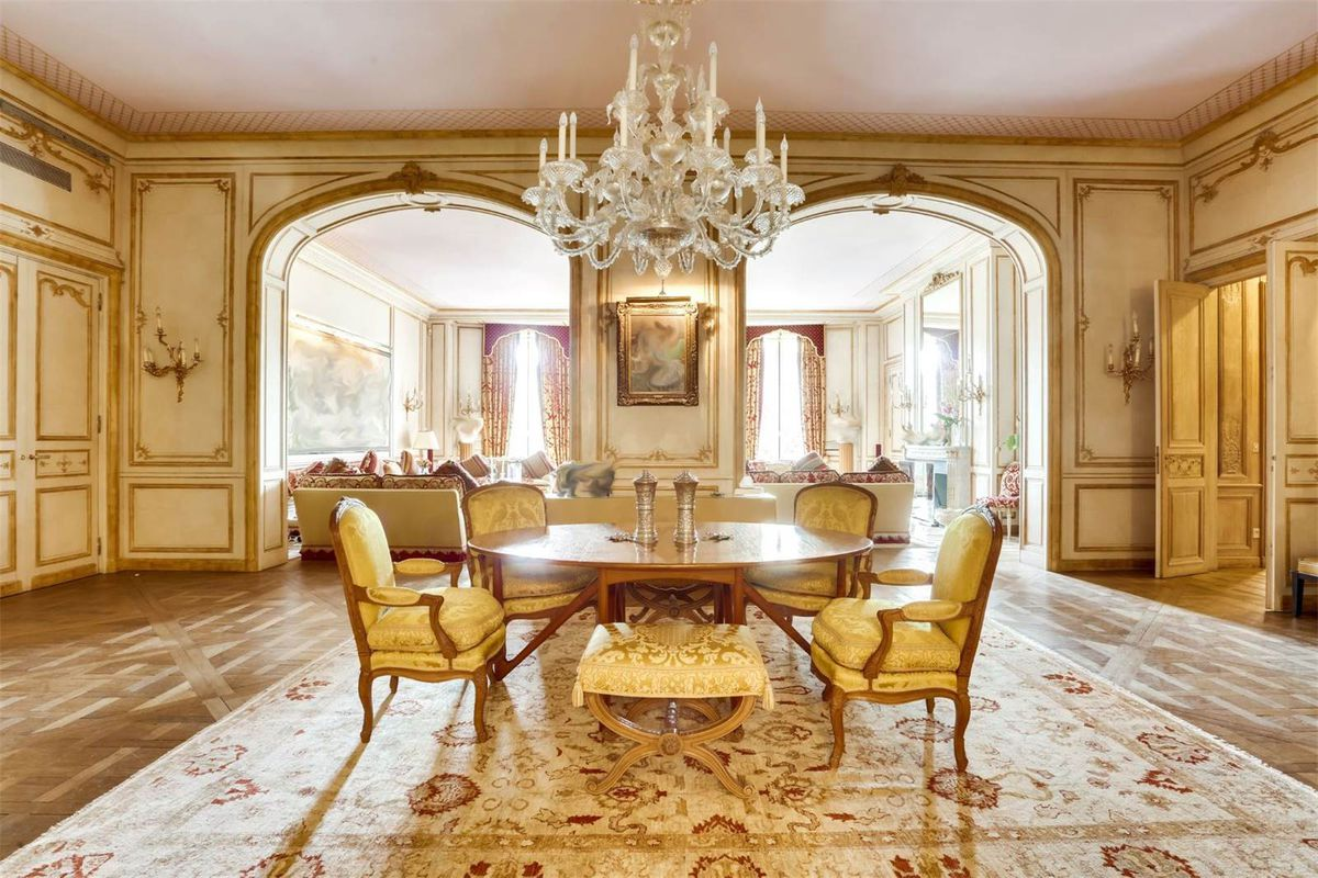 Shot of opulent dining room looking onto sitting room with chandelier, gilded walls, and other ornate trim.