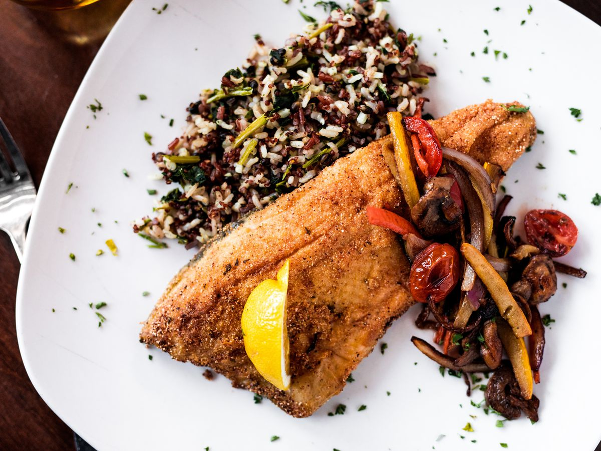 A filet of trout served alongside sautéed vegetables and wild rice