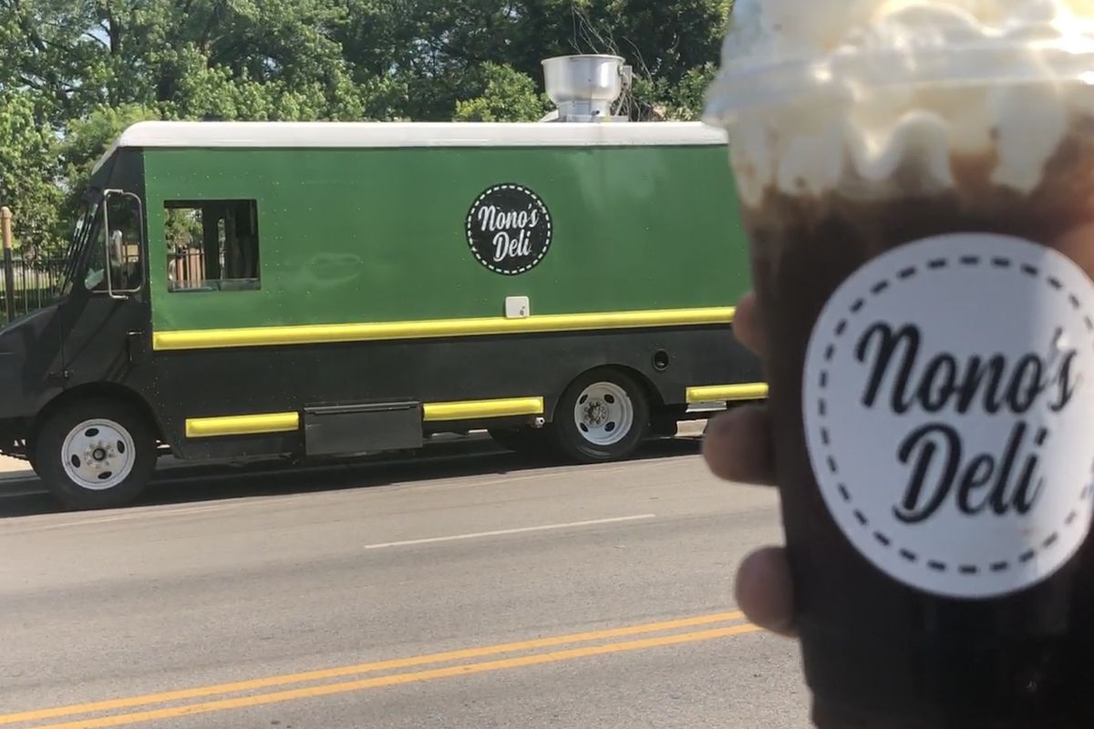 A green food truck and cafe con leche cup.