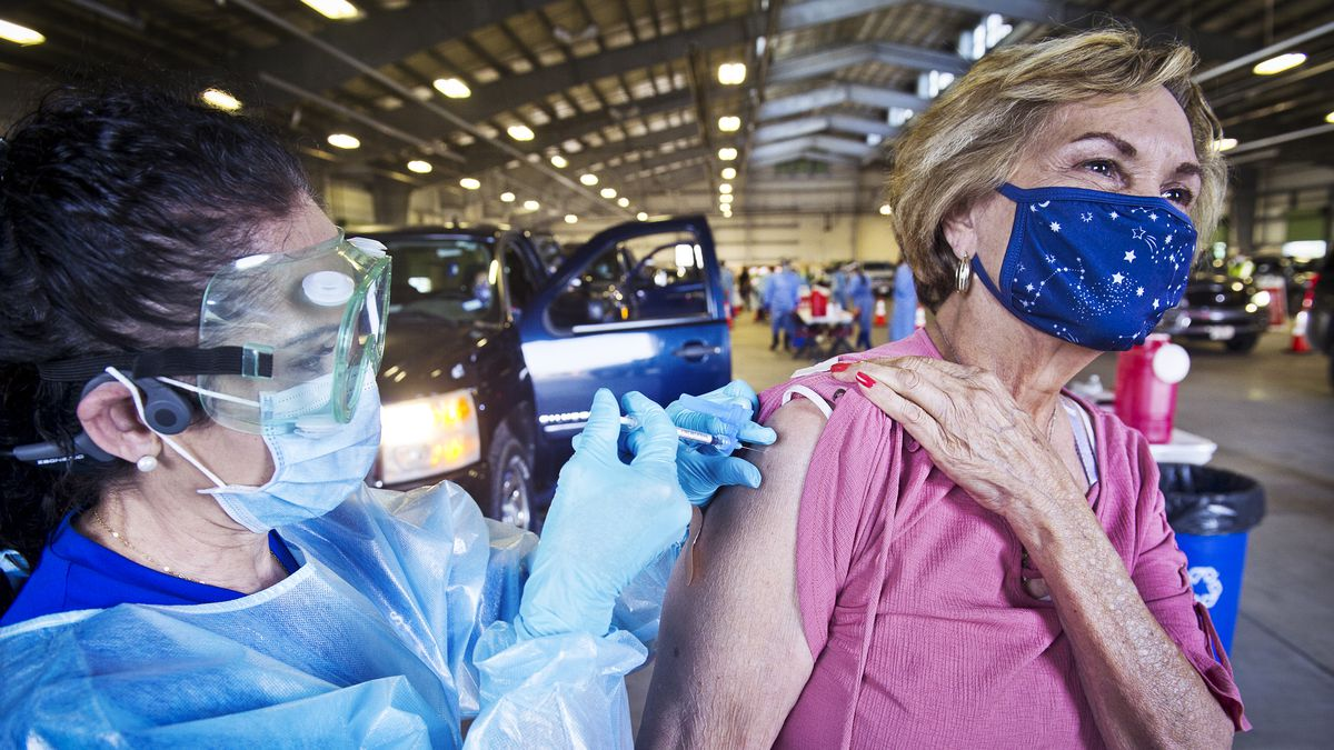 A health care worker giving a masked person a shot in the arm.