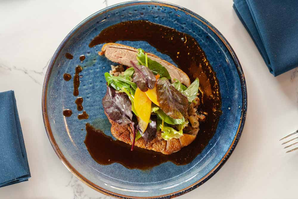 On a blue plate, sliced duck breast is served over dirty rice with a brown sauce around the edges