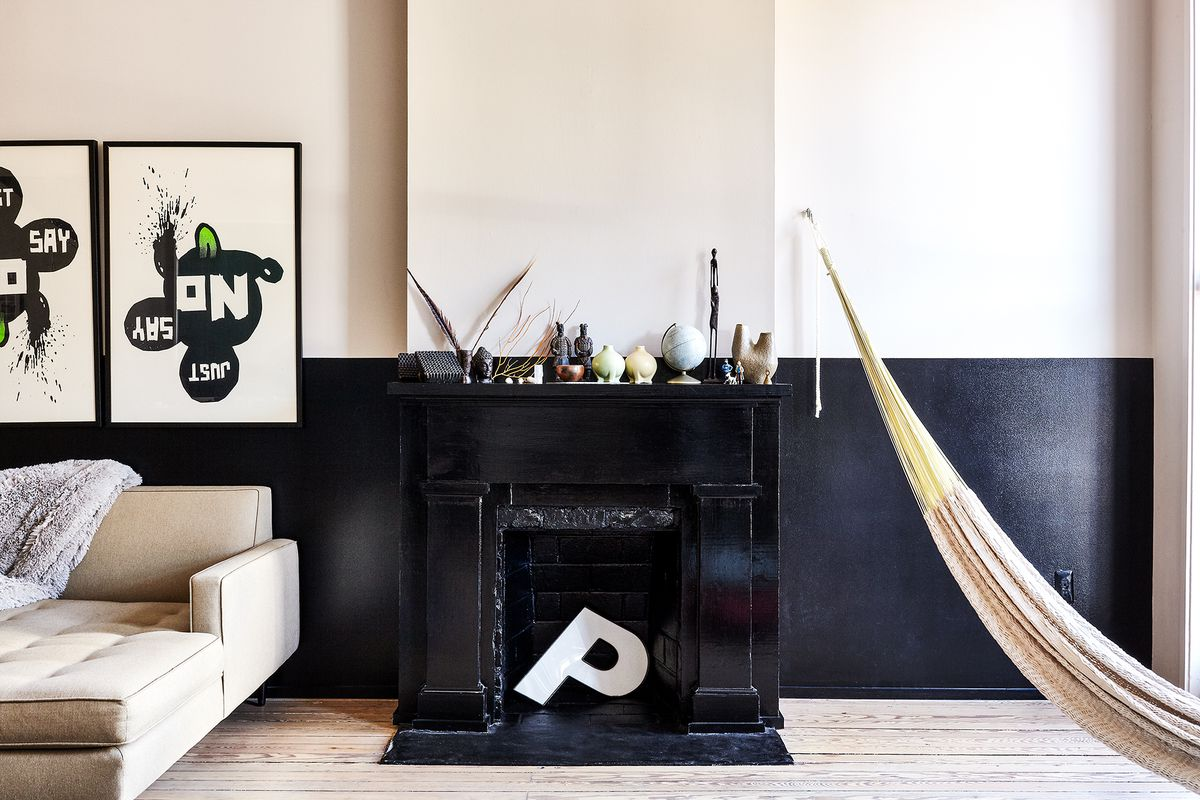 A living area. There is a black fireplace and half of the wall is painted black. There are two works of art hanging on the wall. There is a tan couch. There is a large white letter P inside of the fireplace.