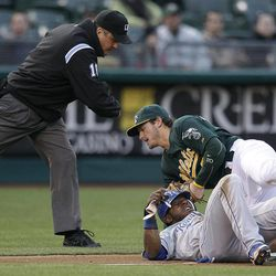 Kansas City Royals' Jason Bourgeois, bottom, collides with Oakland Athletics third baseman Josh Donaldson, top, after being tagged out during the first inning of a baseball game Monday, April 9, 2012, in Oakland, Calif. Bourgeois was attempting to advance on a fly out by Lorenzo Cain. Making the call is third base umpire Mike DiMuro.