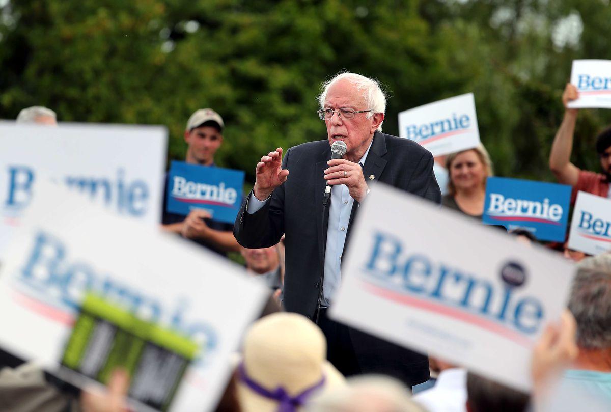 Bernie Sanders speaks to a crowd of people holding Bernie signs.
