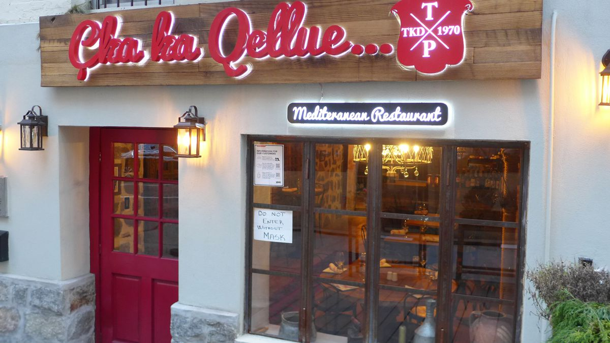 A step down restaurant with a bright lit sign in red Albanian script.