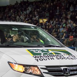 A fundraiser for Washington Youth Soccer involves fans trying to throw mini-soccer balls from the stands into the minivan roof