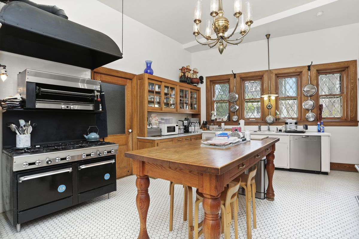 A kitchen has a large table in the middle as an island, a black chef's stove, and cabinets.