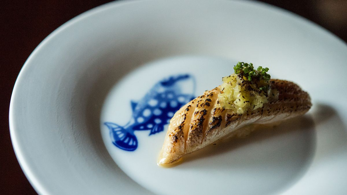 A white plate with a blue fish illustration holds a single piece if hamachi with banana pepper mousse.