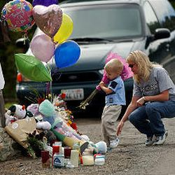 Alex White and mother Alisa place flowers on a memorial for the Robles children, who were hit by a car as they played.