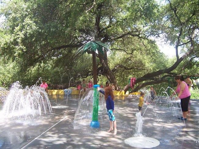 Kids and adults playing in a splash pad shaded by big trees